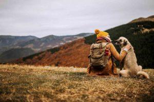 Nainen ja koira vaeltamassa